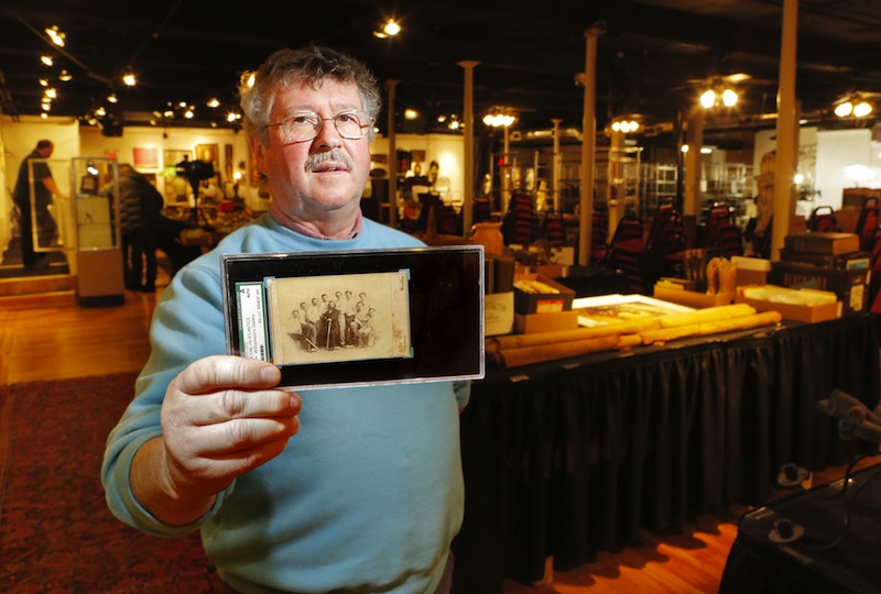 Floyd Hartford, owner of the Saco River Auction Co., holds an 1865 card of the Brooklyn Atlantics baseball team. The card will be auctioned on Wednesday, Feb. 6, 2013.
