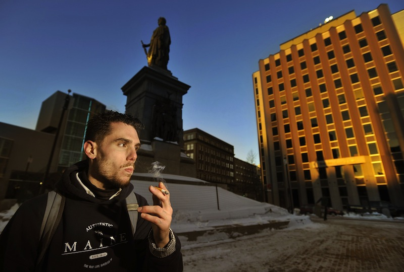 In this Jan. 7, 2012 file photo, Jason Lemay, 26, of Portland, smokes a cigarette in Monument Square. The Portland City Council on Monday, Feb. 5, 2013 voted to ban smoking in 36 city parks and open spaces, including Monument Square.