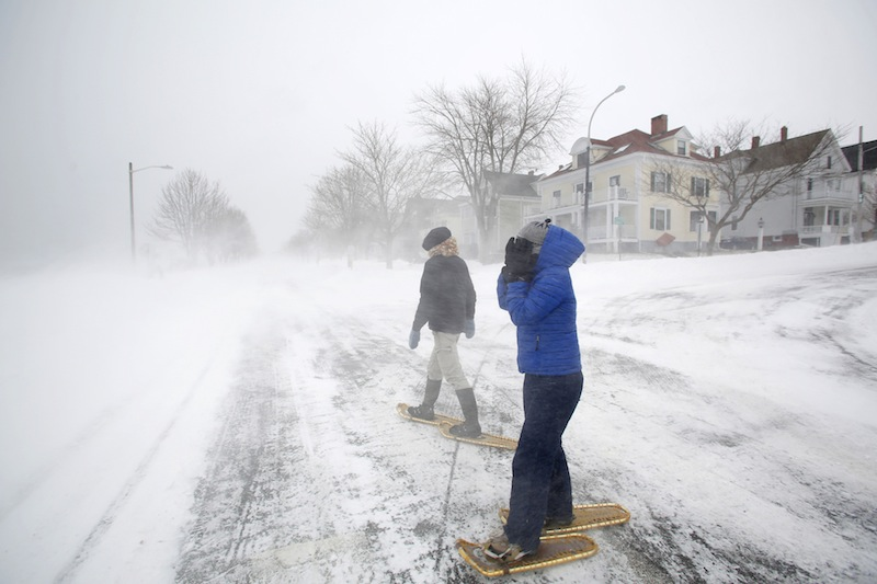 Lucy Sommo, right, of Portland braces herself from the strong winds along the Eastern Promenade while snowshoeing with Jean Geslin during a blizzard on Saturday morning in Portland on February 9, 2013.