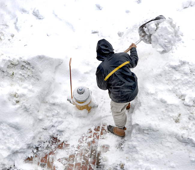 Federal Spice owner and cook Eric Martin does his part by helping the Fire Department clear the hydrant in front of his Federal Street eatery on Monday.