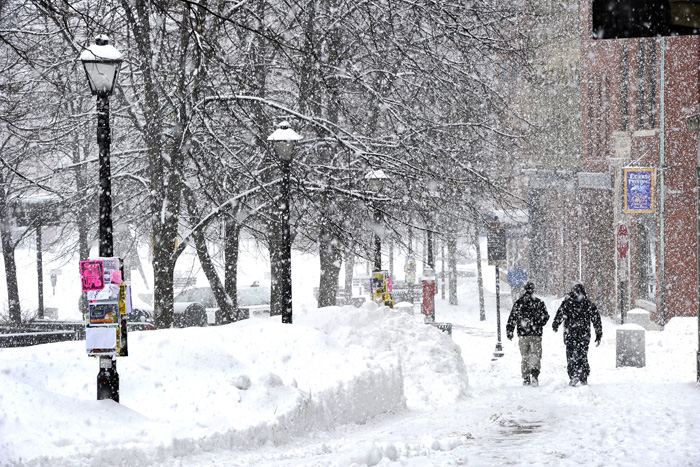 John Patriquin/Staff Photographer: Large snowflakes fell before a freezing rain as Portlanders make their way around the messy streets and sidewalks of intown Portland Monday Feb.11,2013 after a blizzard hit Maine this past weekend. This scene is in Monument Square toward Free st.