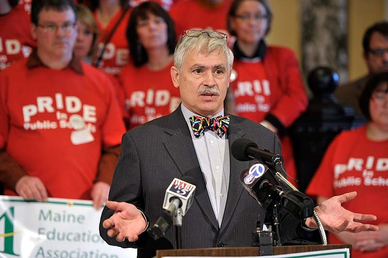 "Sen. Tom Saviello, R-Wilton, speaks to the media about his bill to ease limits on what teachers can do to restrain students in the Capitol rotunda on Wednesday, Feb. 20, 2013. Teachers in the background wear matching red ""Pride in Public Schools"" t-shirts in support of Saviello's bill."