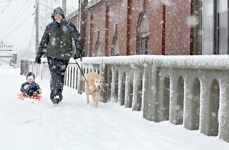 Chris Kessler of South Portland pulls his son Cadence, with his dog Abby, after sledding at Thomas Knight Park in South Portland during the heavy snowfall Sunday morning.