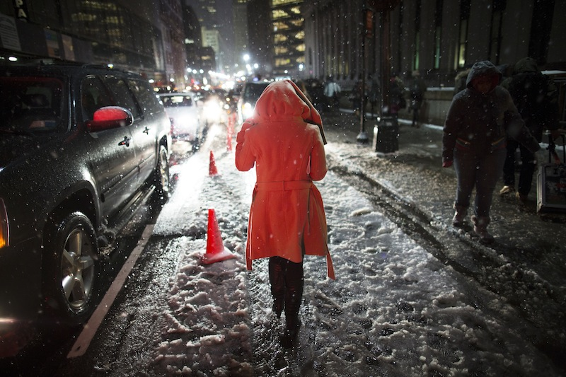 Snow falls on a pedestrian as she leaves the Rag & Bone Fall 2013 fashion collection show during Fashion Week, Friday, Feb. 8, 2013, in New York. Snow began falling across the Northeast on Friday, ushering in what was predicted to be a huge, possibly historic blizzard and sending residents scurrying to stock up on food and gas up their cars. (AP Photo/John Minchillo)