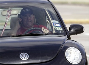 A driver uses a cellphone while driving Wednesday, Dec. 14, 2011, in Houston. A Maine legislative committee voted 10-1 on Tuesday against a bill that would ban most motorists from using handheld cellphones. (AP Photo/David J. Phillip)
