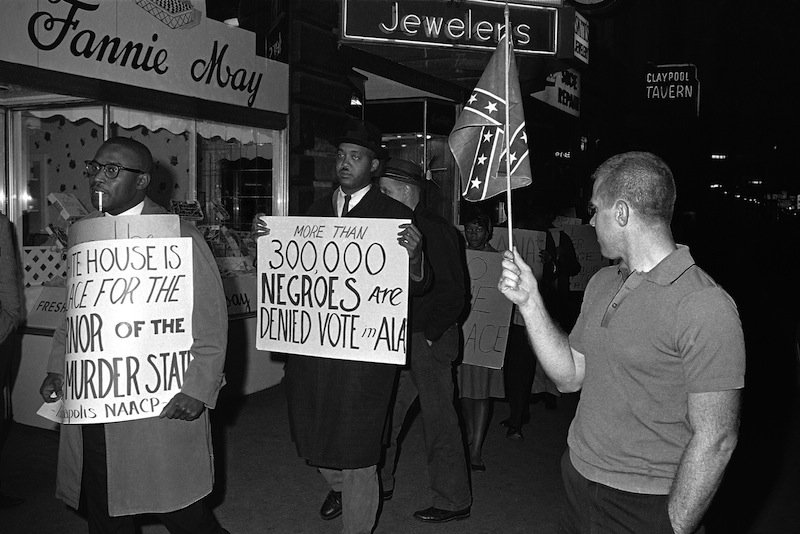 "In this April 14, 1964 black-and-white file photo, a man holds a Confederate flag at right, as demonstrators, including one carrying a sign saying: ""More than 300,000 Negroes are Denied Vote in Ala"", demonstrate in front of an Indianapolis hotel where then-Alabama Governor George Wallace was staying. After more than a century, the Census Bureau is dropping use of the word ""Negro"" to describe black Americans in its surveys. Instead of the term popularized during the Jim Crow era of racial segregation, census forms will use the more modern-day labels, ""black"" or ""African-American"". (AP Photo/Bob Daugherty, File) Walking Holding Placard Text Flag Social Issues Protestor"