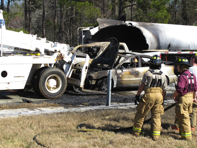Firefighters stand by as a forklift moves a smashed and burned car at the scene where 27 vehicles collided Wednesday, Feb. 6, 2013, on Interstate 16 near Montrose, Ga. More than two dozen cars, pickup trucks and tractor-trailers collided Wednesday morning in a fiery pileup on a foggy Georgia interstate 16, killing at least three people and sending nine others to a hospital, officials said. (AP Photyo/Russ Bynum)