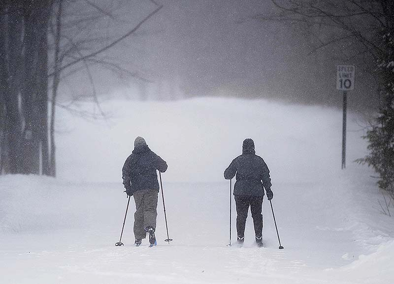 Skiers put fresh tracks on Quarry Road as snow falls in Waterville on Saturday.