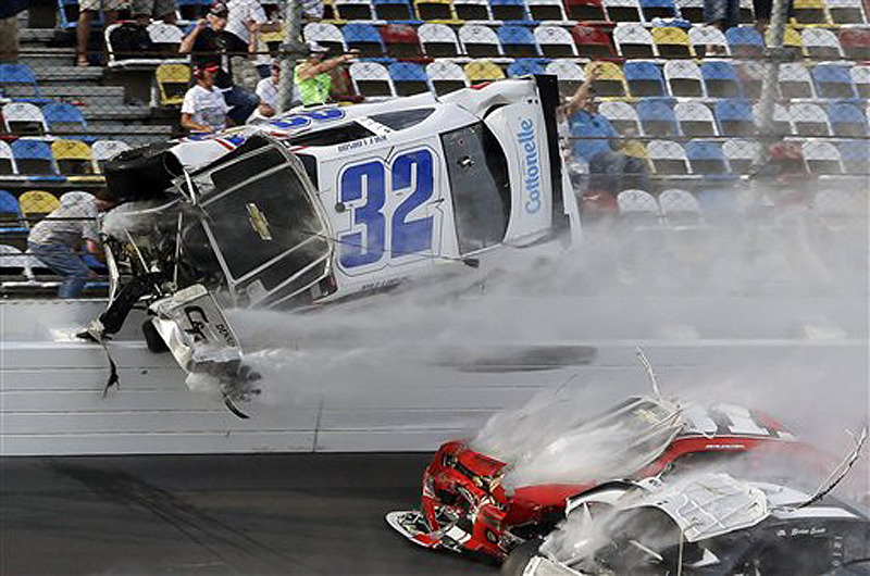 Kyle Larson (32) goes airborne and into the catch fence during a multicar crash involving Justin Allgaier (31), Brian Scott (2) and others during the final lap of the NASCAR Nationwide Series auto race Saturday at Daytona International Speedway in Daytona Beach, Fla. The crash sent car parts and other debris flying into the stands, injuring spectators.