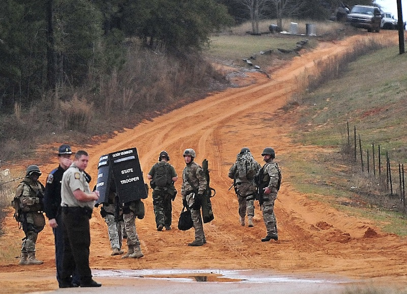 Law enforcement personnel work at check point Wednesday, Jan. 30, 2013, in Midland City, Ala., near the home where the Tuesday's school bus shooting suspect is barricaded in a bunker with a young child as hostage. Police, SWAT teams and negotiators were at a rural property where a man was believed to be holed up in a homemade bunker Wednesday after fatally shooting the driver of a school bus and fleeing with a 6-year-old child passenger, authorities said. (AP Photo/The Dothan Eagle, Jay Hare) BUS SHOOTING;MIDLAND CITY