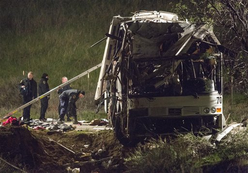 Investigators early Monday work at the scene of the crash that killed at least eight people and injured 38 near Yucaipa, Calif.