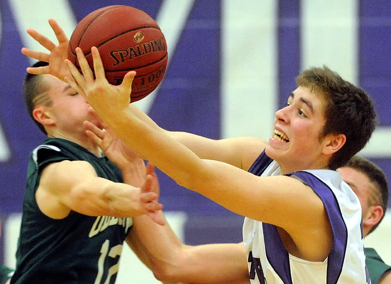 Old Town High School's Cam Archer, 12, left, and Waterville Senior High School's Owen Brown, 32, battle for the loose ball in the second half in the Class B preliminary play-off game in Waterville Wednesday night, Waterville defeated Old Town 75-33.