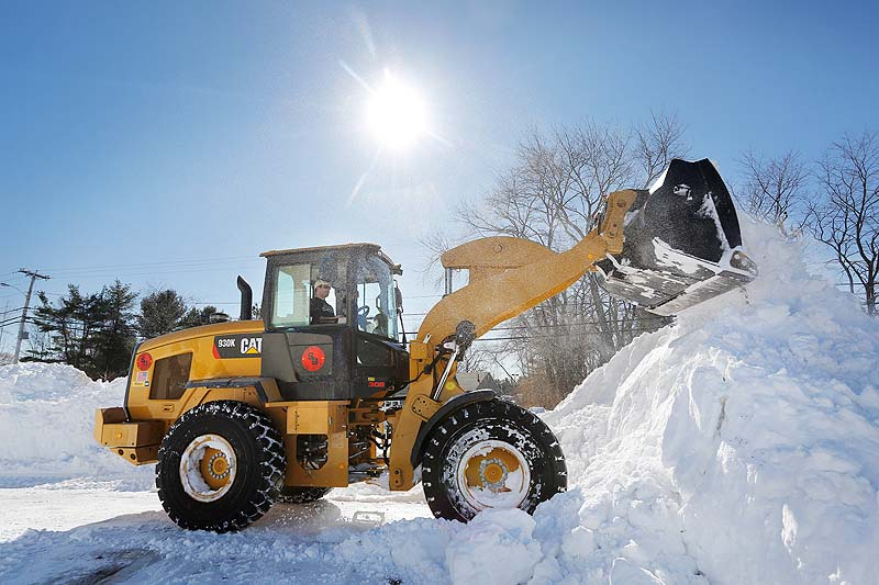 Chris Massey of Cornish operates a loader on Sunday at a shopping plaza in Falmouth, while removing snow for Shaw Brothers Construction.
