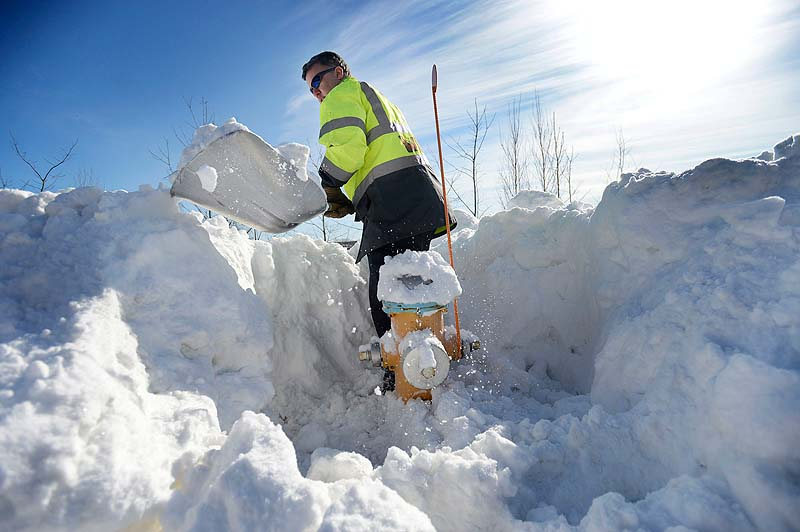Portland firefighter Eric Weeks shovels out a fire hydrant on West Commercial Street in Portland on Sunday.