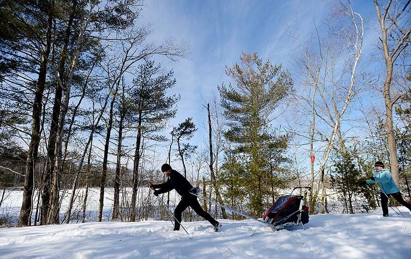 Chris and Kim Nichols of Scarborough cross-country ski along the Eastern Trail in Scarborough on Sunday. Chris is pulling his 9-month-old daughter, Lily, in a tow on skis.