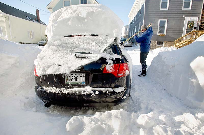 A large snowdrift rests on the top of the car of Joshua Hamel as he cleans off his car in Portland on Sunday, the day after Blizzard Nemo.