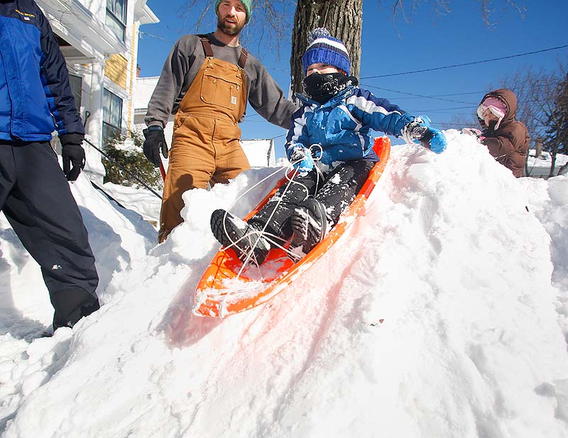 Charlie Creswell, 4, sleds down a hill created by the snowplows on Fessenden Street in Portland on Sunday.