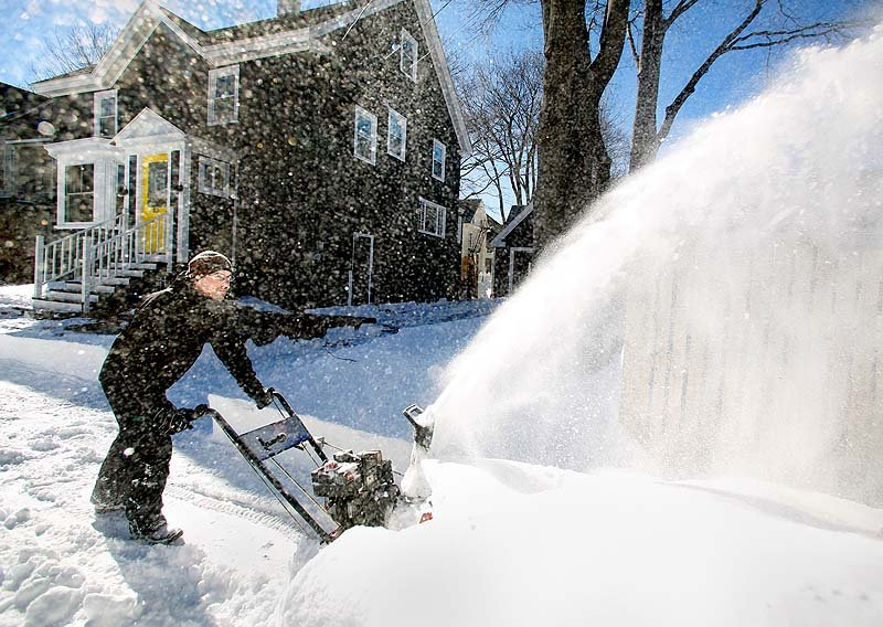 Mike Carey blows the snow off his driveway on Oakdale Street in Portland during the cleanup from a blizzard on Sunday.