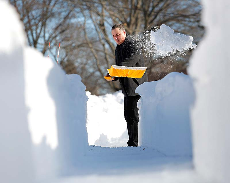 Jerry Hunter shovels his walkway in Portland on Sunday after a weekend storm brought 31.9 inches of snow to the city.