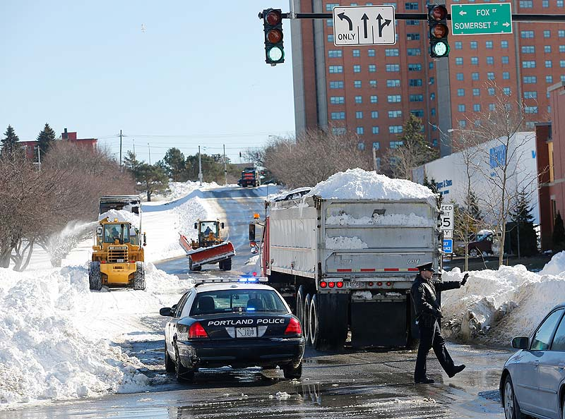 A section of Franklin Street in Portland is closed off Sunday as trucks bring in snow from around the city to be deposited in the median after a weekend storm brought 31.9 inches of snow to the city.