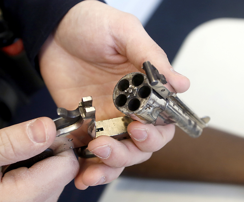 A Yarmouth police officer displays a .32-caliber revolver that was turned in to the department Saturday.