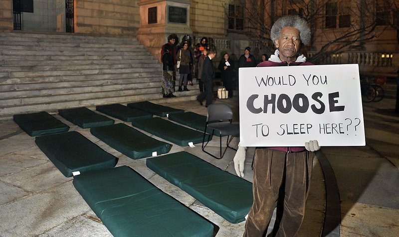 Nick Nicholson with Homeless Voices for Justice stands near mats used by homeless people to sleep on at shelters during a November vigil outside Portland City Hall.