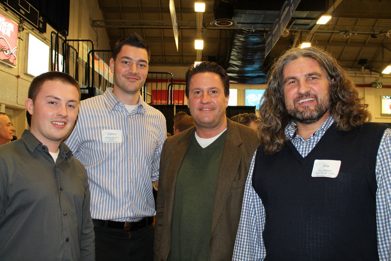 """Fairpoint Communications' Adam Roy, Andrew """"D.J. Drew"""" Woodford and Scott Dimick join Guy Mitchell of Time Warner Business Class in a bit of revelry courtside at the Portland Expo Wednesday night."""