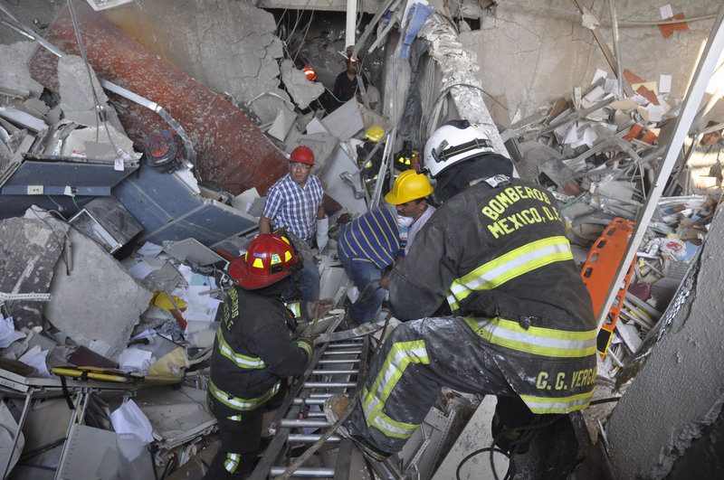 Firefighters and workers dig for survivors following an explosion at a building next to the 52-story tower of Petroleos Mexicanos, or Pemex, in Mexico City on Thursday.