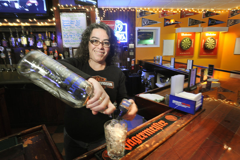 Bartender Laurie Lavertu mixes a drink at The Frosty Pint in Portland. The bar is owned by a veteran whose dream was to open a sports bar reminiscent of the famed sitcom bar Cheers.