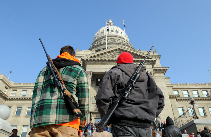 Chance Novak, 18, left, and his father, Chet, both of Boise, stand outside the Idaho Statehouse in Boise after a pro-gun rally Jan. 19, as part of Gun Appreciation Day events held around the country.