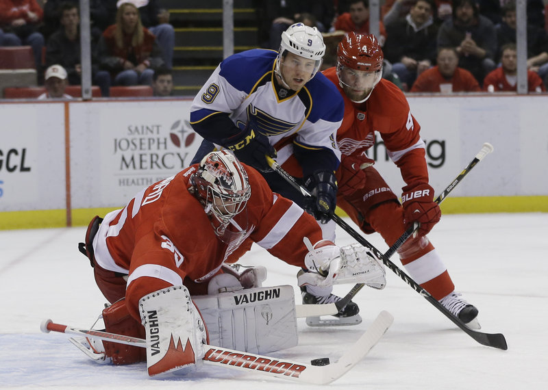 Detroit goaltender Jimmy Howard reaches for the puck while teammate Jakub Kindl guards against St. Louis center Jaden Schwartz during Friday's NHL game in Detroit, won by the Red Wings.