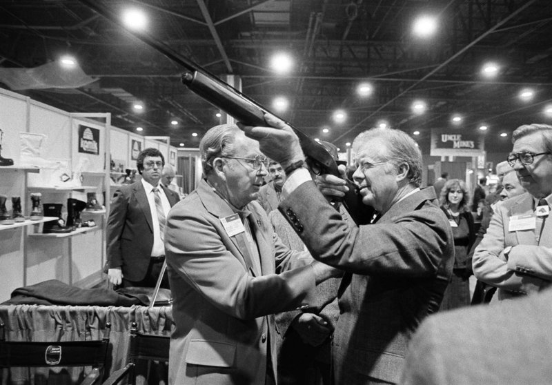 Former President Jimmy Carter sights down the barrel of a shotgun at a gun show in Atlanta in 1984.