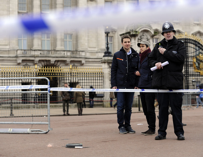 An area is cordoned off Sunday outside Buckingham Palace in London after police used a stun gun to subdue a man armed with two knives. Queen Elizabeth II and Prince Philip were not at the palace at the time.