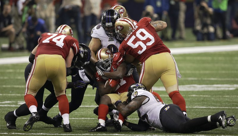 San Francisco running back Frank Gore, center, is tackled by Baltimore's Terrell Suggs, right, and Ma'ake Kemoeatu. Gore rushed for 110 yards and a touchdown, but the 49ers' second-half comeback bid fell short.