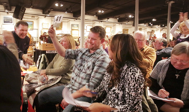 Jason LeBlanc of Newburyport, Mass. holds up his bid card after winning the 1865 Brooklyn Atlantics baseball card at the Saco River Auction Company in Biddeford on Wednesday, February 6, 2013. LeBlanc's winning bid was $80,000 but he'll end up paying $92,000 for the card after paying a buyer's premium. At left is LeBlanc's mother Denise Leblanc and at right, his girlfriend Melinda Yung.