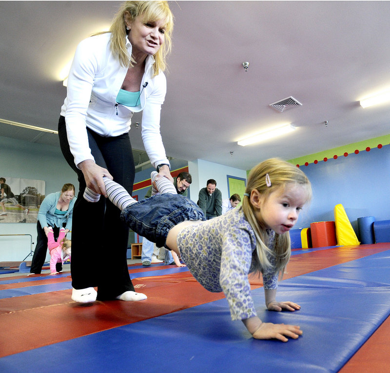 Kim DeMado conducts an exercise class in March 2012 with then-3-year-old Rachael Cohen from Cumberland and other toddlers and parents at Tumble Tikes Children's Fitness Center in Portland. DeMado and her husband, Tim, launched the center after becoming parents in 2009.