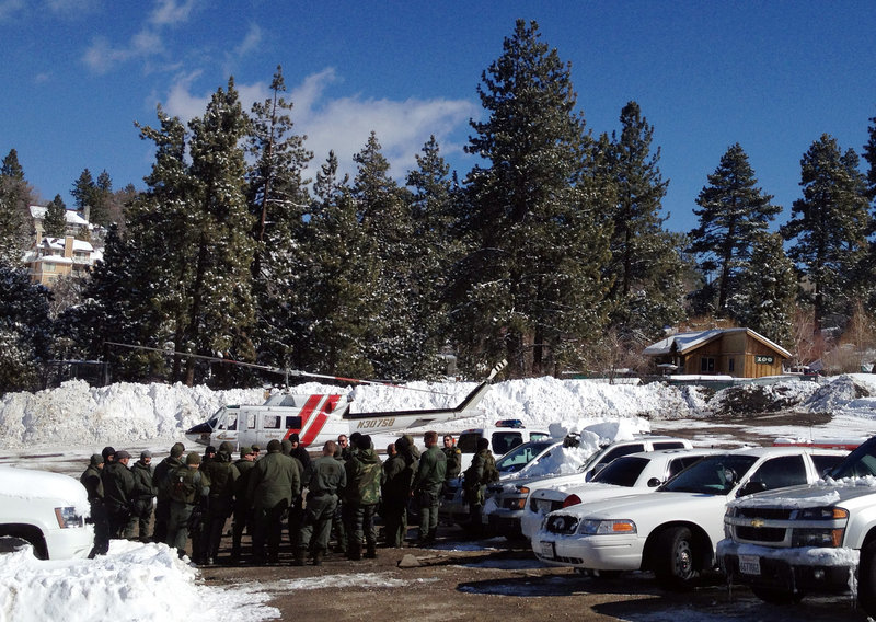 Law enforcement officials gather Saturday near Big Bear, Calif., to discuss the search for Christopher Dorner, suspected in the slayings of those he blamed for ending his police career.