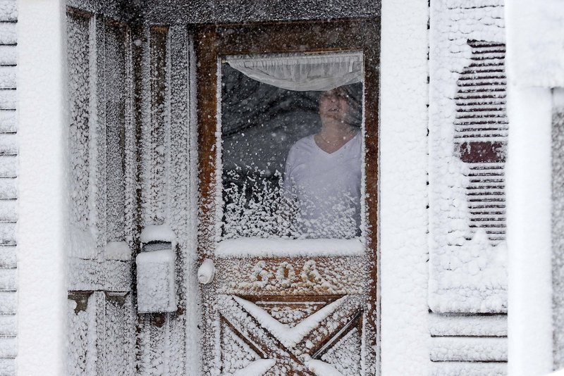 A resident of Third Street in South Boston looks out of his snow-coated front door Saturday.