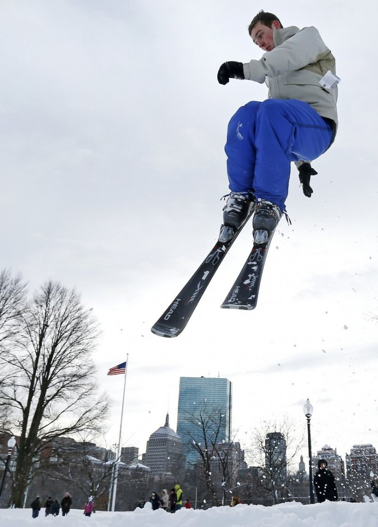 Thomas Kolek, a Northeastern University student from Westford, Mass., spins a helicopter jump while skiing on Boston Common in Boston on Saturday. The Boston area got about 2 feet of snow.