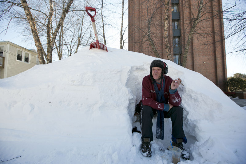 Bert Johnson takes a break while clearing snow from a bus-stop bench outside the apartment complex where he lives.