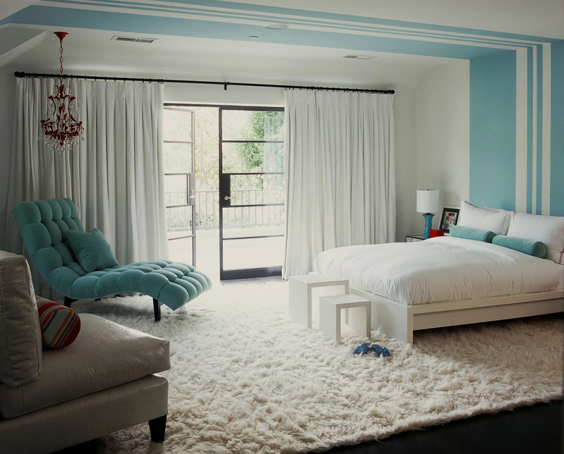 White and blue walls and a snow-white flotaki rug define Betsy Burnham's guest bedroom.