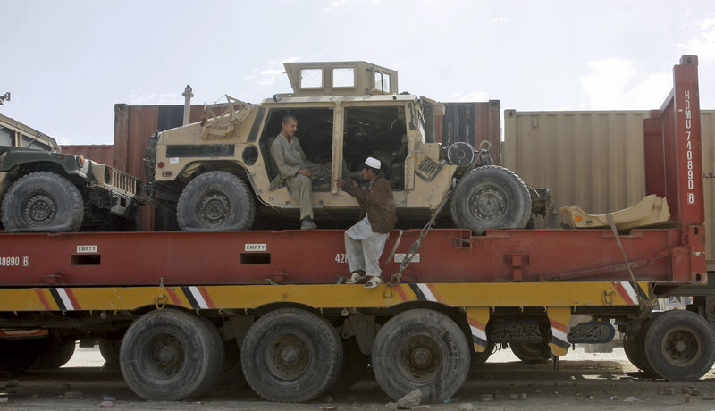 Pakistani driver assistants talk while sitting on a truck carrying NATO Humvees at a terminal on the Afghan border in Chaman, Pakistan, on Monday. The U.S. has started using the land route through Pakistan to pull military equipment out of Afghanistan.
