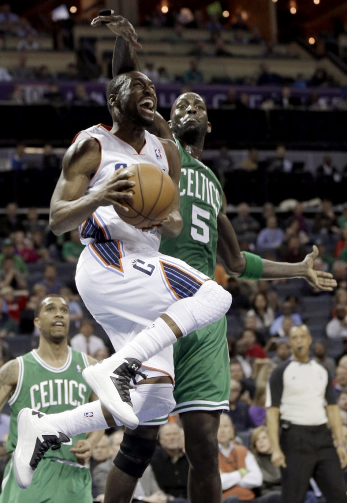 Kemba Walker drives past Boston's Kevin Garnett during the first half of Charlotte's 94-91 win Monday, ending the Celtics' seven-game winning streak.