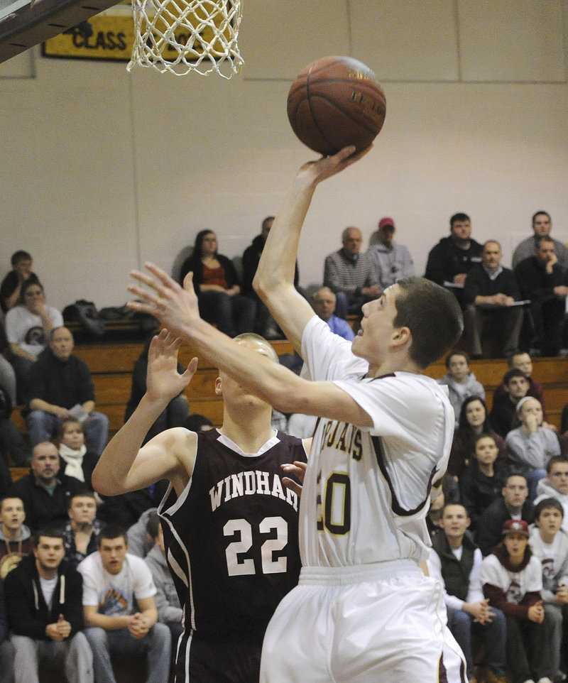 Evan Wright of Thornton Academy finds room inside Tuesday night to shoot while guarded by Dylan Weisser of Windham.