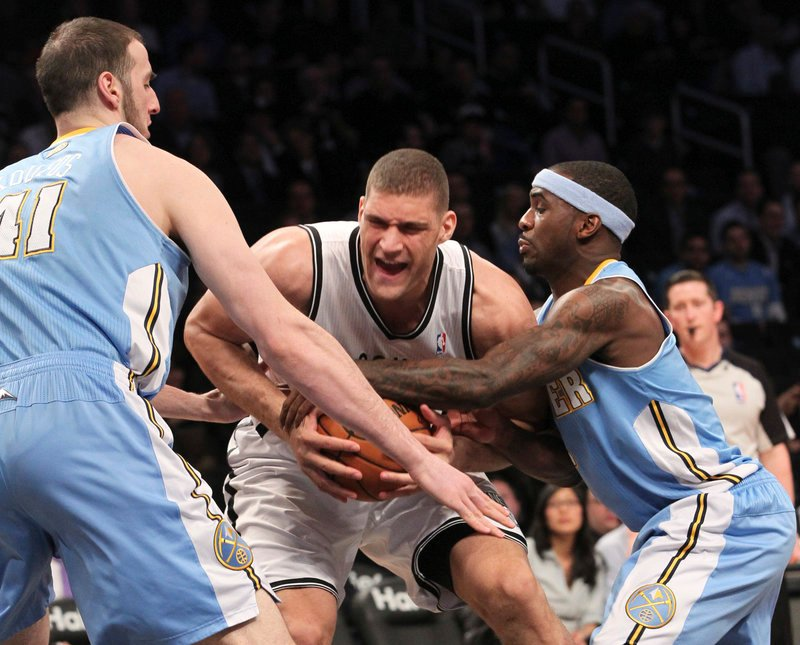 Brooklyn's Brook Lopez fights for a loose ball against Denver's Kosta Koufos, left, and Ty Lawson during the Nets' 119-108 win over the Nuggets at New York on Wednesday.