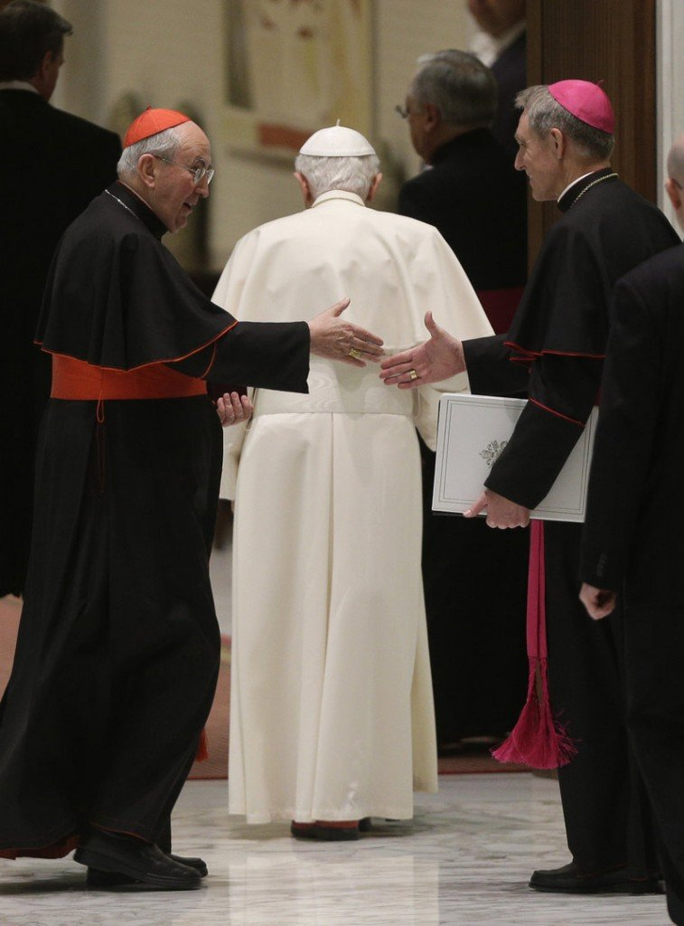 Cardinal Agostino Vallini, left, and the pope's personal secretary, Georg Gaenswein, shake hands as Pope Benedict XVI leaves after an audience with Roman clergy Thursday.