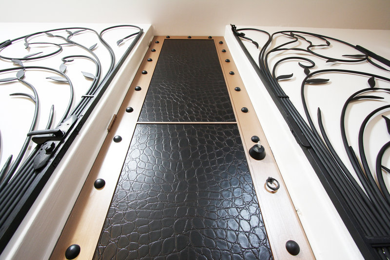 Bonded leather in an oversized crocodile design covers a cellar door.