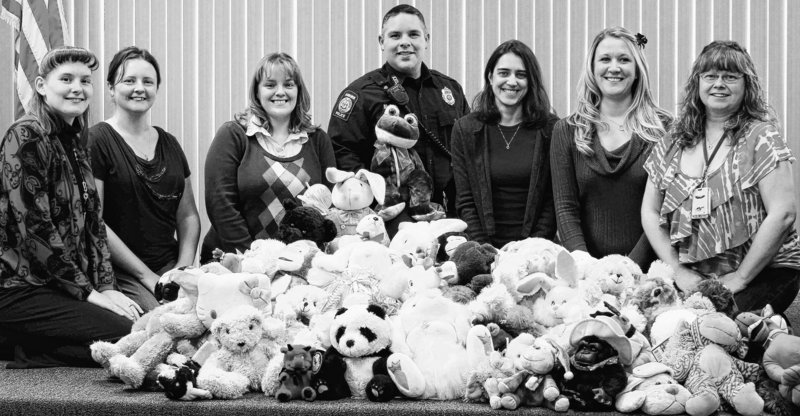 Employees of FISC Solutions presented more than 100 new stuffed animals to Auburn School Resource Officer Marshall McCamish, center, for distribution to children that police officers may come in contact with at traumatic times. Pictured, from left, are Joanna Champagne, Nicole Bergeron, Alenna James, McCamish, Jessica Vachon, Jenn Dudzic and Kandy Baldinelli.