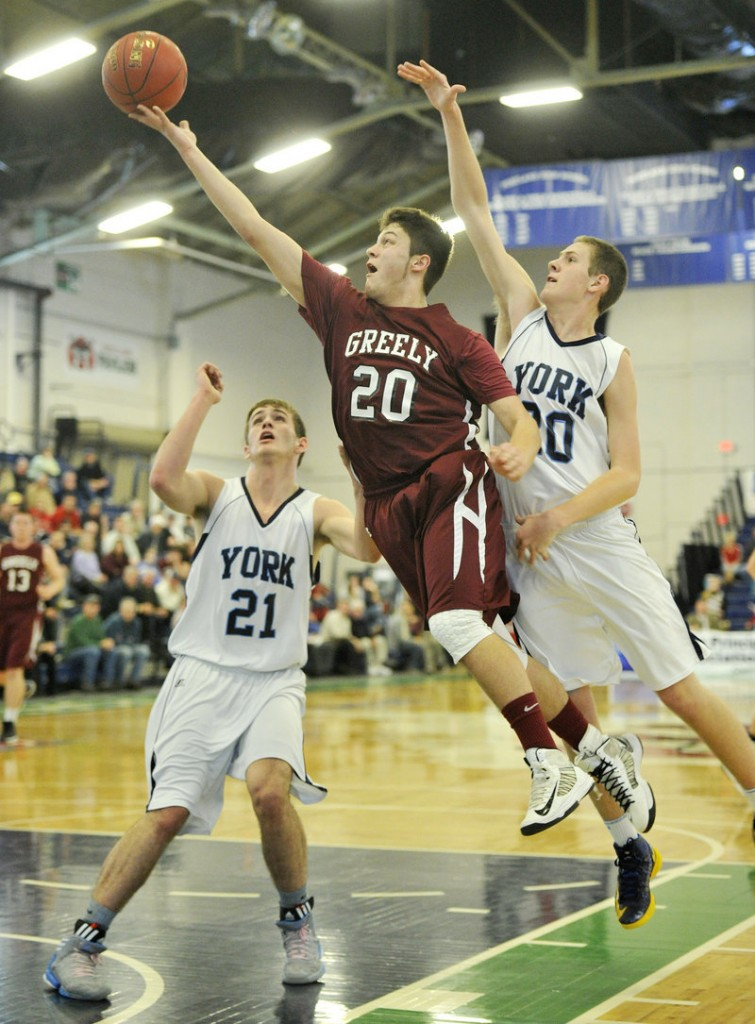 Jonah Normandeau of Greely scoops the ball toward the basket past Aaron Todd, left, and Adam Bailey of York during York's 64-38 victory in a Class B quarterfinal at the Expo.