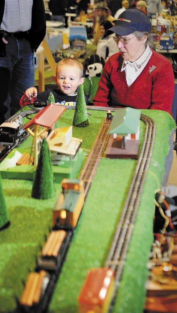 Connor Ruttenberg, 2, of Turner pushes the button to unload logs from a model railroad with some help from Joanne Burns of Friendship at the Maine 3-Railers display Saturday in Augusta.